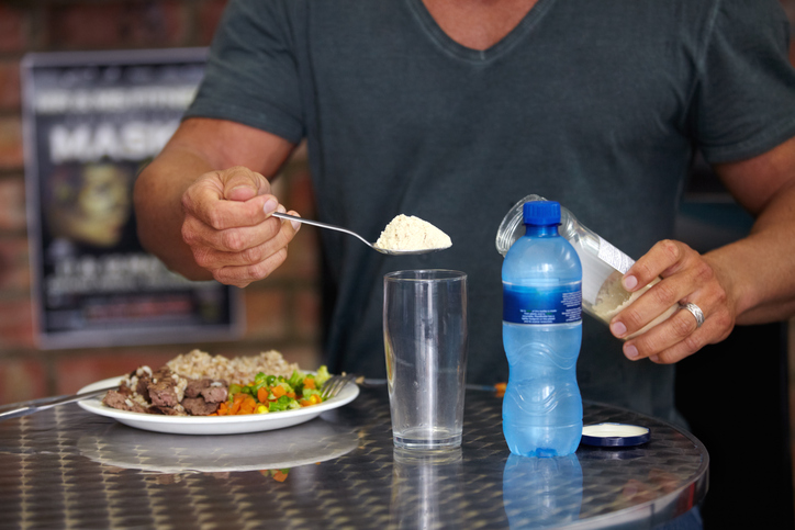 A bodybuilder adding supplements to his water while eating a protein-heavy meal